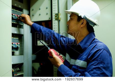 Engineer turning on switch in the electrical cabinet at control room with selective focus