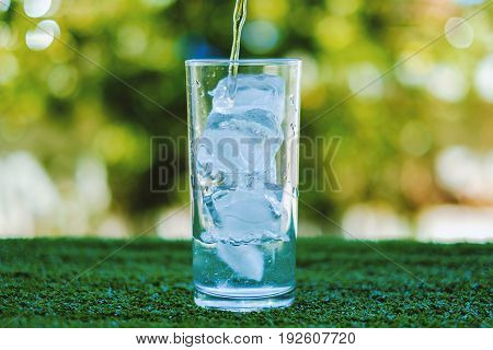 Pouring water into a glass of ice with blurred natural green background and added color filter