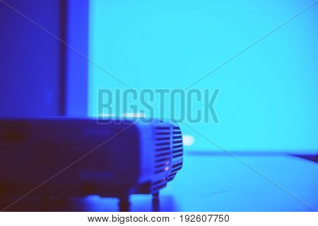 Screen with blue light from projector in the dark meeting room