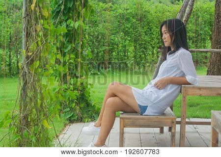 Relaxation Concept : Asian woman sitting on wooden chair at outdoor garden. She relaxing and looking forward with green natural background.