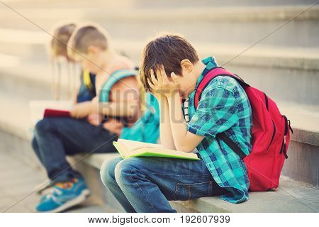 Children with rucksacks sitting on the stairs near school. Pupils with books and backpacks outdoors