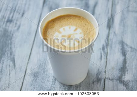 Clock picture on latte foam. White paper cup with coffee. Best time to drink coffee.