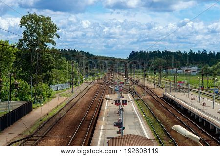 Railroad against beautiful sky at sunset. Industrial landscape with railway station, colorful blue sky, trees and grass, yellow sunlight. Railway junction. Heavy industry.