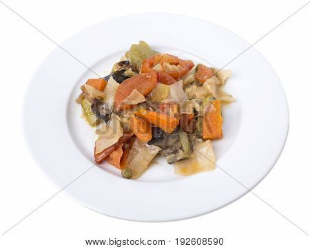 Closeup of vegetable ragout made of cooked eggplants with cabbage and carrots on a round plate. Isolated on a white background.