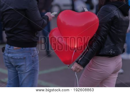 Romantic meeting of guy and girl. Two LED balloons in the form of scarlet burning hearts in the evening in the girl's hand. For a romantic background. Concept of love, Valentine's Day,