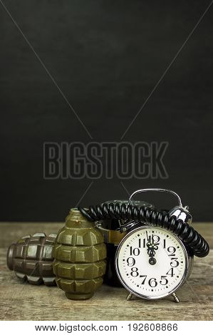 Grenade and old alarm clock. Timed bomb.