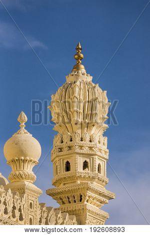 Mysore India - October 26 2013: Cream yellow stone corner minaret of upper structure Tipu Sultan mausoleum. Golden Kalasam on top deep blue sky.