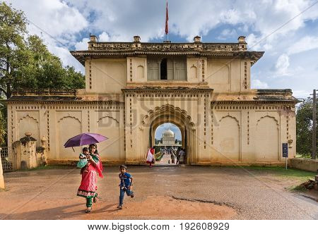 Mysore India - October 26 2013: Beige gate structure with black mold to Tipu Sultan mausoleum grounds. Mausoleum visible through gate. mother with children in foreground. Cloudy blue sky.