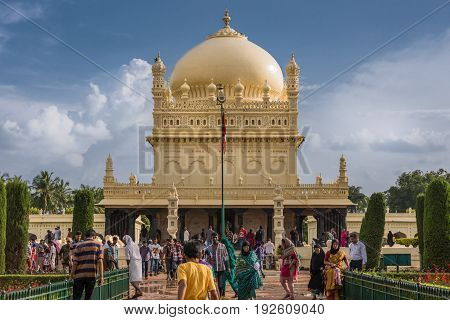 Mysore India - October 26 2013: Cream yellow Tipu Sultan mausoleum with dome under heavy cloudscape. People walking to and from the building. Green and red from park.