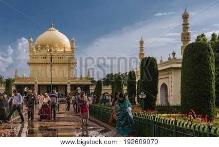 Mysore India - October 26 2013: Cream yellow Tipu Sultan mausoleum with dome and mosque under heavy cloudscape. People walking to and from the buildings. Green and red from park.