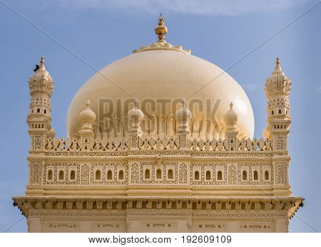 Mysore India - October 26 2013: Upper structure and dome of cream yellow Tipu Sultan mausoleum under blue sky. Golden Kalasam on top. One black bird.