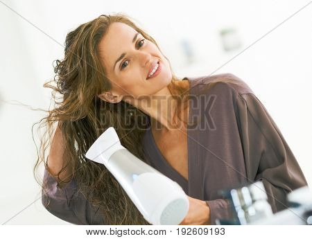 Happy Young Woman Blow Drying Hair In Bathroom