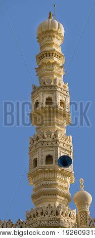 Mysore India - October 26 2013:Closeup of cream yellow minaret of mosque at Tipu Sultan mausoleum under deep blue sky. Sound system.
