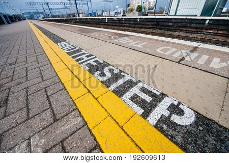 Mind the step yellow text line in British train station - visiting United kingdom taking care and security measures while traveling with train