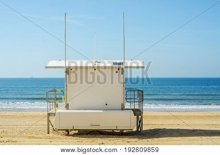White Rescue Hut On A Sandy Beach, Safe Relax By The Ocean, A Beautiful Sunny Day