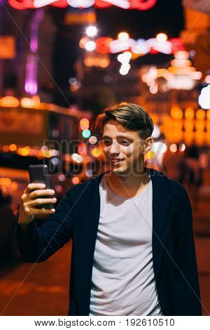 Young man take photo on smartphone while walking in night city streets. Smiling guy on blurred lights background
