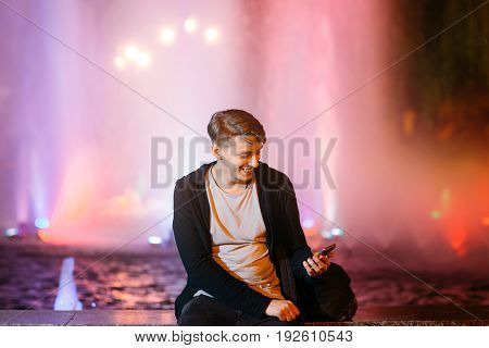 Handsome young man using smartphone while walking in night city streets. Smiling guy reading message outdoor