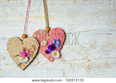two hearts decorated with small wild flowers hang on a rope and copy space on an old wooden painted background for your text