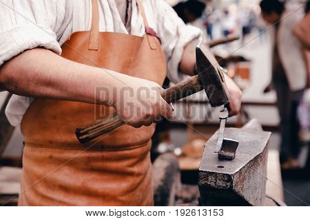 The smith is operating a hammer in a blacksmith's workshop on the anvil, holding the workpiece with pliers. Concept work on metal in the traditions.