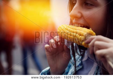 girl is eating yellow boiled corn outdoors. Smile close-up. The concept is useful food on the street
