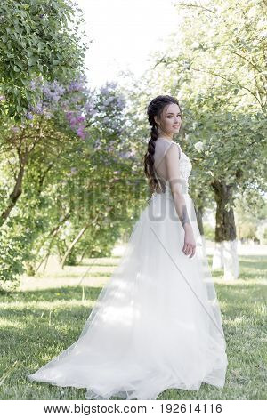 Tender beautiful cute girl bride in a white air dress with a bouquet of lilacs in her hands walking through the park on a sunny spring day. Photo in gentle colors