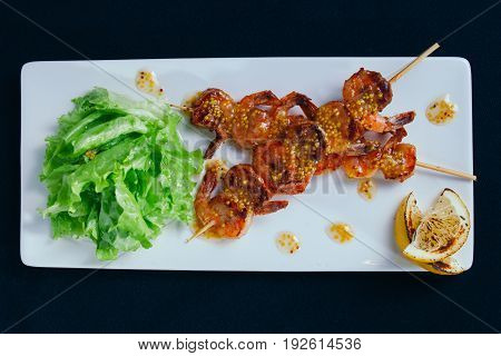 Grilling fresh shrimp on wooden skewers on white plate. Black background