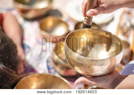 Woman Playing A Singing Bowls Also Known As Tibetan Singing Bowls, Himalayan Bowls. Making Sound Mas