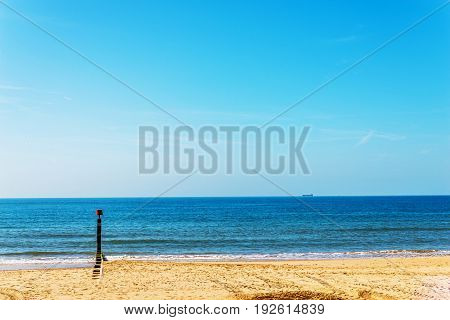 Dock Pilings On A Sandy Beach, Blue Ocean And Yellow Sand, Sunny Hot Day In Seaside Resort