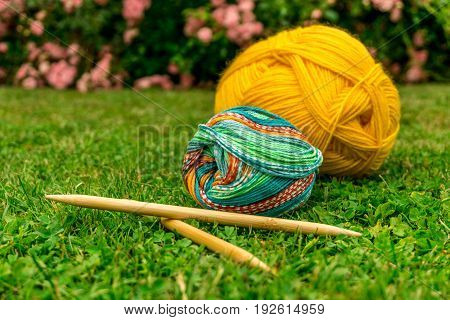 Knitting wool for summer on green lawn in sunshine with needles