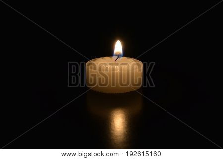 A single tea light candle burning on a dark table
