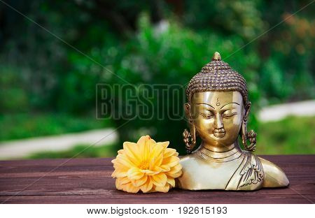 Golden antique Buddha statue on a blurred green background. Buddha and flowers. Concept religion. Copy space