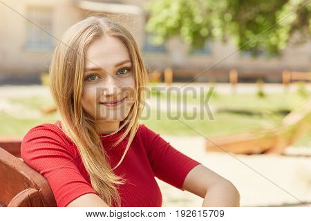 Young Schoolgirl With Blonde Hair And Alluring Appearance In Red Elegant Dress Sitting Outdoors On W