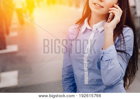 Close-up of a tourist girl holding in hands and talking on the phone, a means of communication. no one. The concept is always in touch.