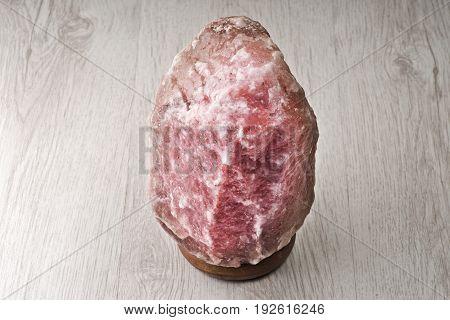 Pink salt lamp isolated on wood table