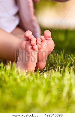 Baby feet in the green grass at summer warm day in the city park. Cute part of baby body. Close-up and vertical photo. Babies backgrounds. Concept of the happy babies.