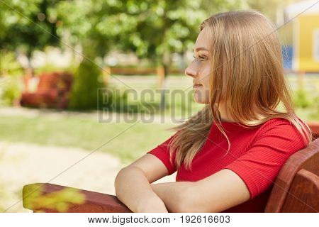 Sideways Portrait Of Thoughtful Pretty Girl With Light Lustrous Hair Dressed In Red Clothes Looking