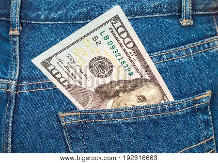 One hundred dollars bill sticking out of the blue jeans pocket