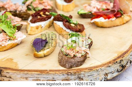 Different sandwiches with meat and fresh vegetables on wooden board