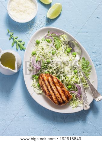 Grilled chicken breast and cabbage green pea and parmesan salad. Healthy balanced food. On a blue background top view