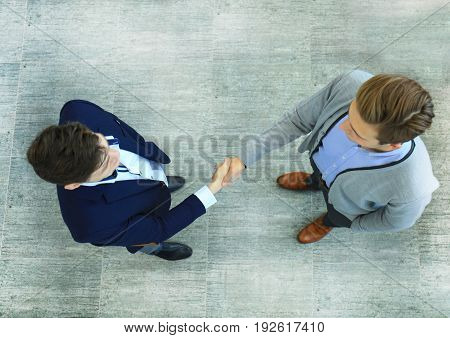 Top view of a two businessman shaking hands. Welcome to business