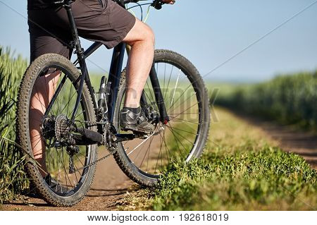 Closeup of cyclist man legs with mountain bike on outdoor trail in the summer field. Young cyclist dressed in the sportwear and sporty shoes. Sporty backgrounds. Horizontal photo. Concept of the healthy and active lifestyle.