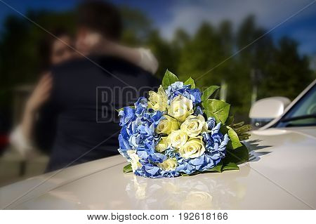 Bridal bouquet on a wedding car. In the background hugging the bride and groom blurry