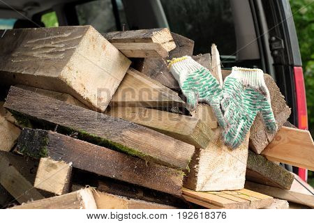 Stack of firewood in a car boot with protection gloves on a top