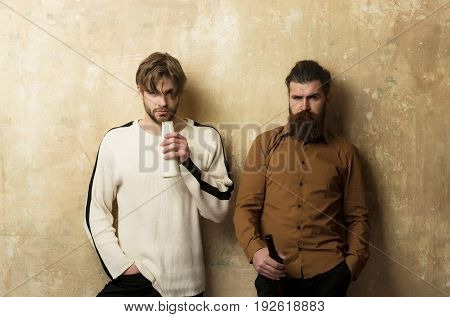 Two Serious Friends In Casual Wear Standing With Bottles