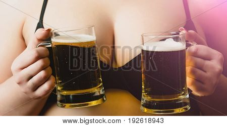 beer or lager with foam in two glass mugs in female hands on sexy black bra supporting female breast or bust. Alcohol and refresher. Bad habits addiction and desire