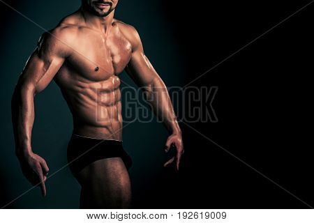 athlete with muscular body and strong torso of bodybuilder in underwear pants posing with bare chest and belly on grey background sport and training copy space