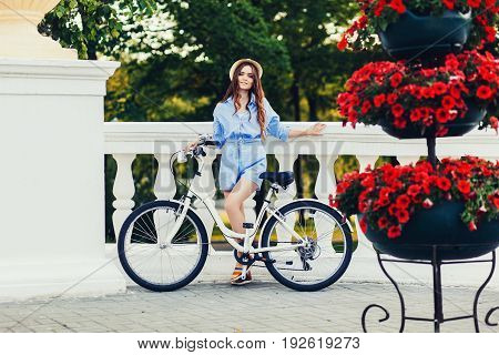 Charming woman with a bicycle near the bright flowers in the city