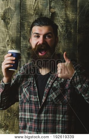 takeaway coffee. Happy bearded man or brutal caucasian hipster with grey hair long beard and moustache showing thumbs up gesture with plastic cup on wooden background. Healthy lifestyle and dieting