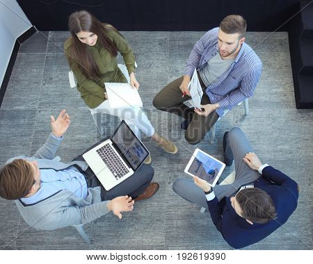 Top view of working business group sitting during corporate meeting