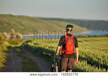 Rear view of the young cyclist with mountain bicyclist in the summer meadow. Sportsman dressed in the black sportwear, with helmet and backpack. Beautiful landscape like a background. Concept of the healthy and active lifestyle.